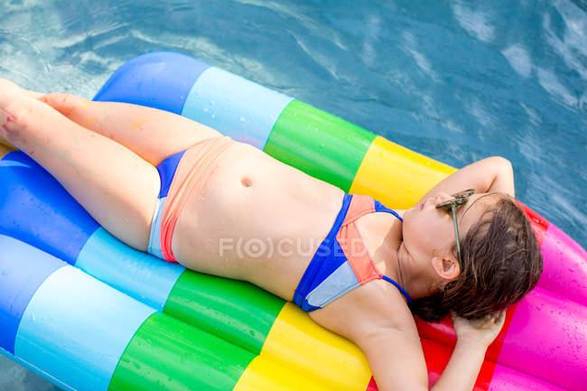 Menina em biquíni deitado em inflável na piscina exterior — Fotografia de Stock