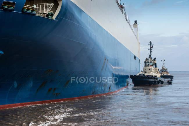 Cropped image of Tugs pushing car ship — Stock Photo