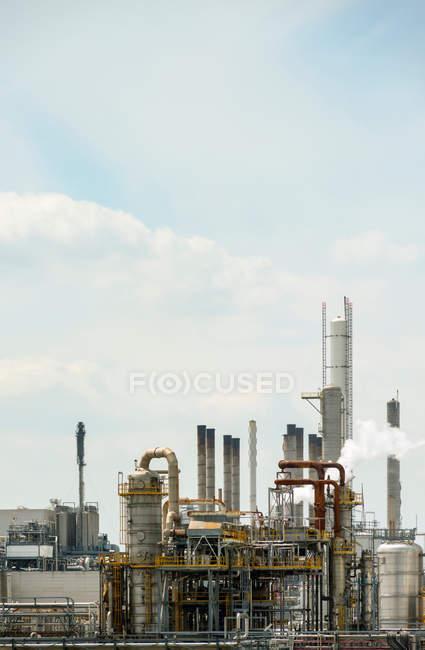 Fábrica construida estructura con tubos y cielo azul - foto de stock