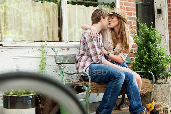 Молодая пара поцелуи на скамейке — стоковое фото