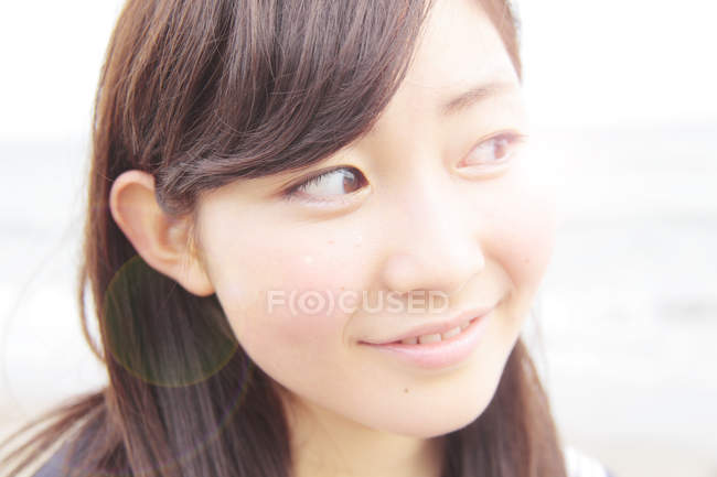 Portrait of young woman, looking away and smiling — Stock Photo