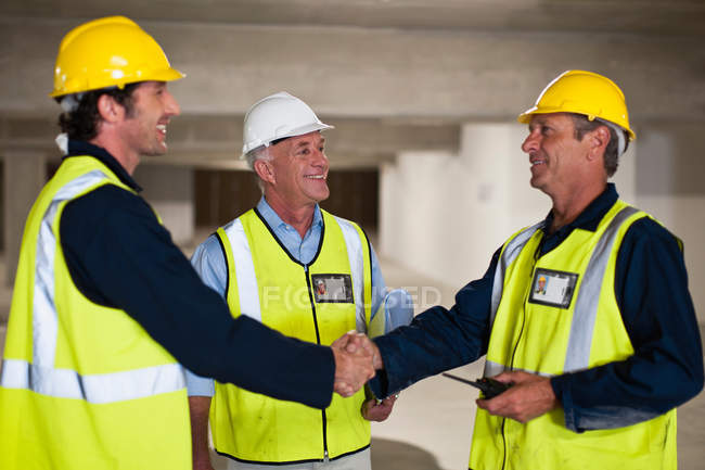 Workers shaking hands on site — Stock Photo