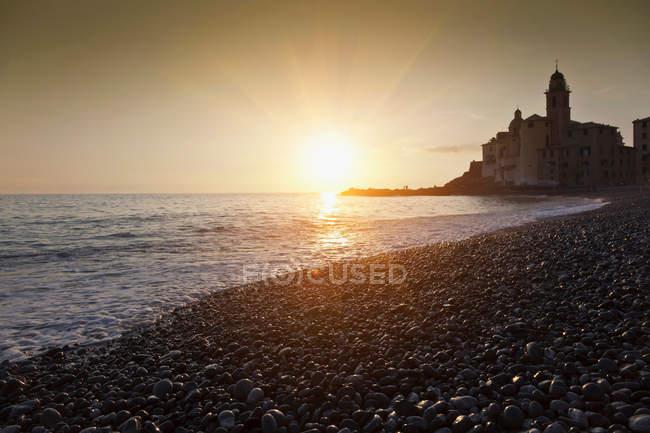Tramonto sulla spiaggia rocciosa — Foto stock