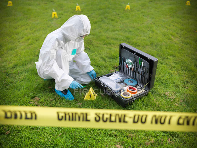 Forensic scientist inspecting toolkit at crime scene, police tape in foreground — Stock Photo