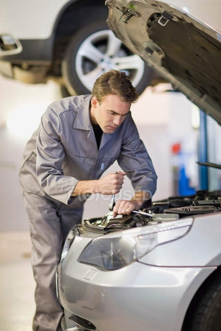 Meccanico di lavoro sul motore auto in garage — Foto stock