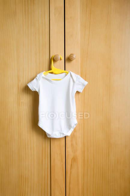 Babygro висить на дерев'яні гардероб — стокове фото