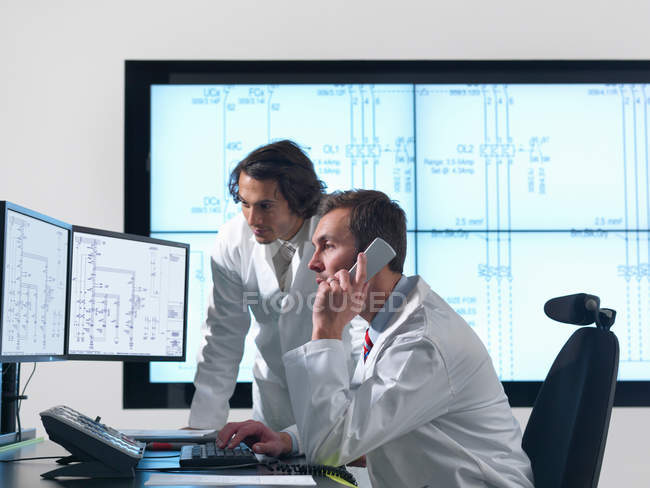 Scientists with diagrams on screens — Stock Photo