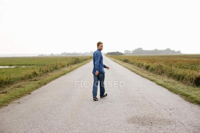 Man walking on rural road — Stock Photo