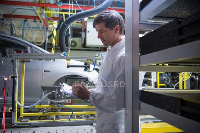 Рабочий осмотр автомобиля на автомобильном заводе — стоковое фото