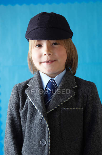 Boy in school uniform smiling at camera with a toothy grin — Stock Photo