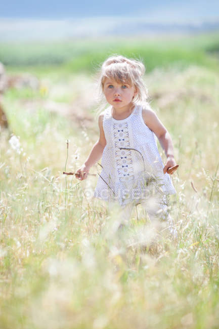 Girl walking in tall grass — Stock Photo