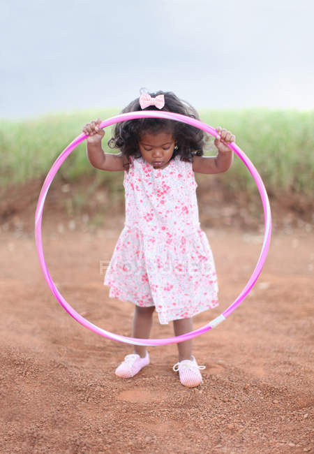 Girl playing with hula hoop on dirt road — стокове фото