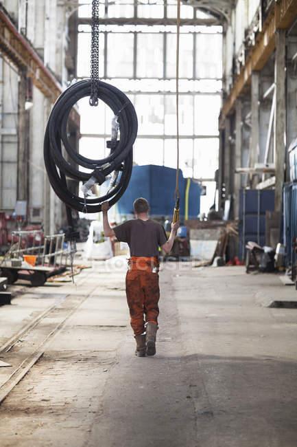 Задній вид працівник потягнувши трубопроводів лебідка в майстерні суднобудівний завод — стокове фото