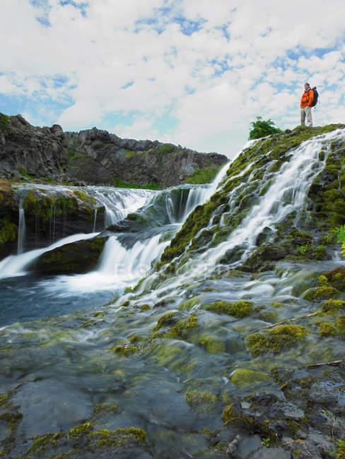 Hiker admiring rocky waterfall — Stock Photo