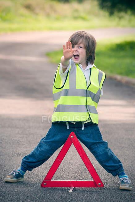 Menino brincando de trabalhador de trânsito na estrada rural — Fotografia de Stock