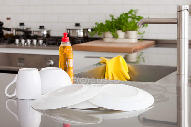 Close-up view of dishes, cup, detergent and sink in kitchen — Stock Photo