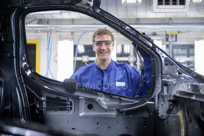 Portrait of worker wearing boiler suit and protective goggles in car factory — Stock Photo