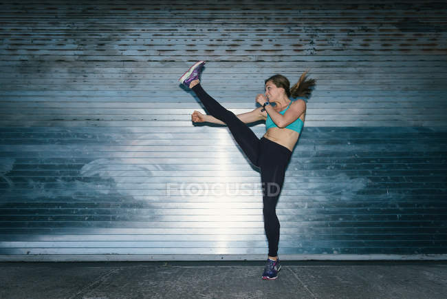 Young woman, working out, doing high kick, outdoors, at night — Stock Photo