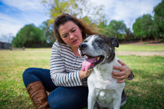 Mature woman petting old dog in park — Stock Photo