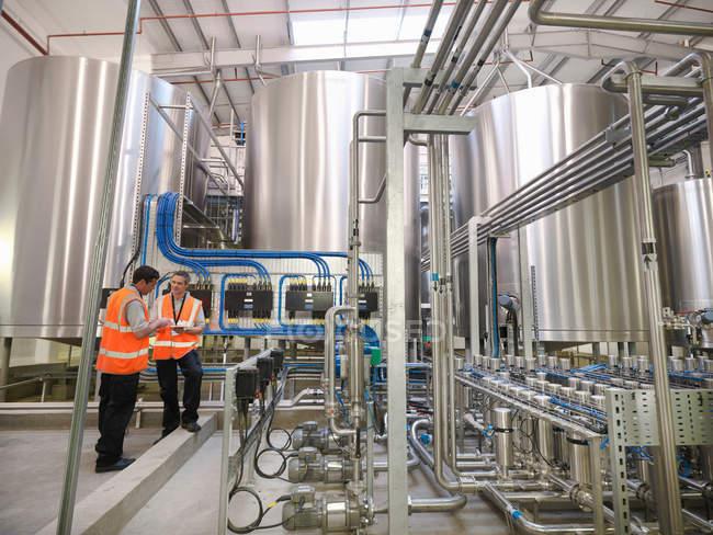 Рабочие завода осматривают резервуары ? — стоковое фото