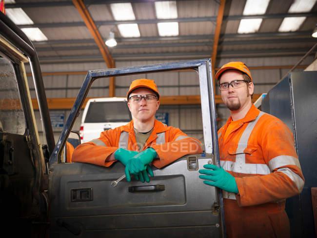 Engenheiros aprendizes trabalhando no carro — Fotografia de Stock
