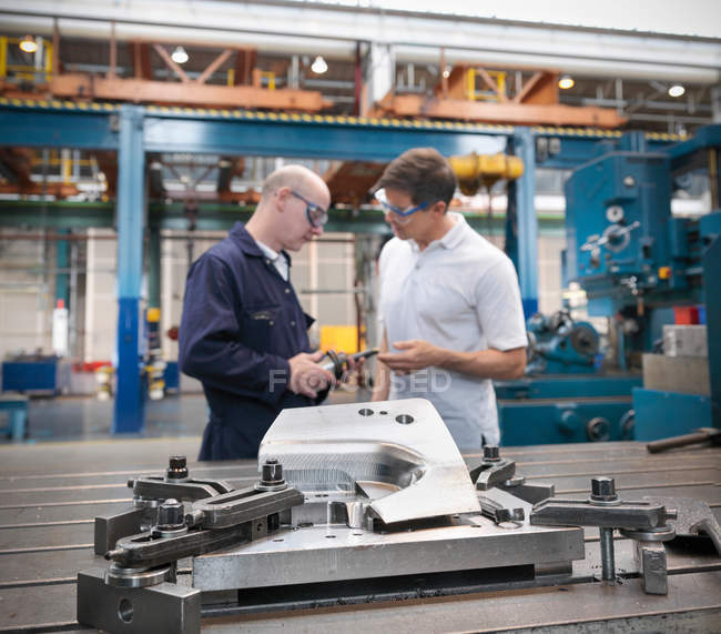 Engineers discussing car parts in car factory — Stock Photo