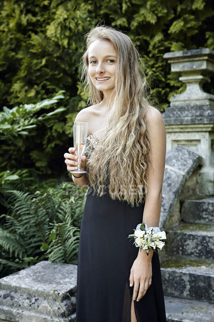 Teenage girl wearing prom dress and corsage holding champagne flute looking at camera smiling — Stock Photo