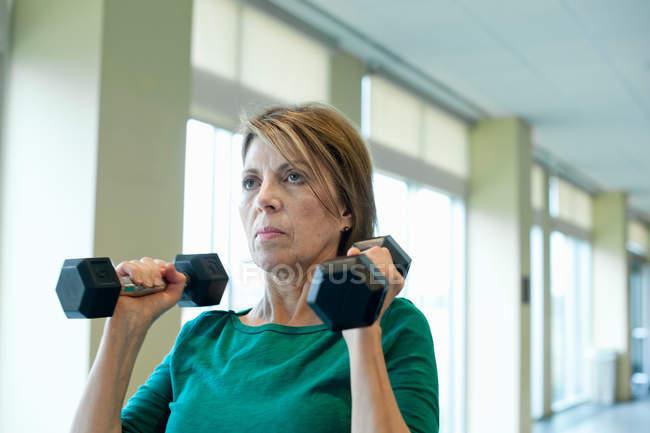 Ältere Frau im Fitnessstudio Gewichte heben — Stockfoto
