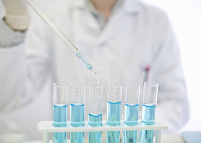 Scientist pipetting liquid in test tubes, cropped shot — Stock Photo