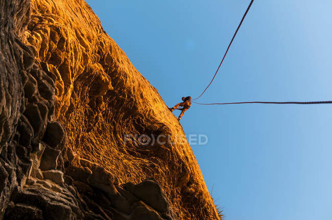 Rock climber scaling steep rock face — Stock Photo