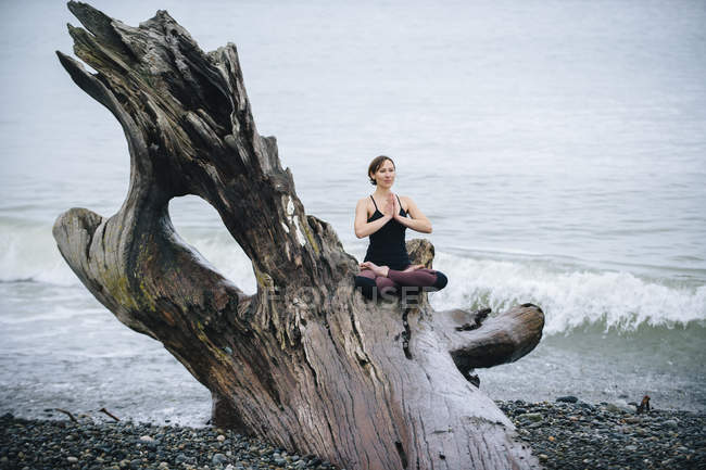Mature woman practicing yoga lotus position on large driftwood tree trunk at beach — Stock Photo