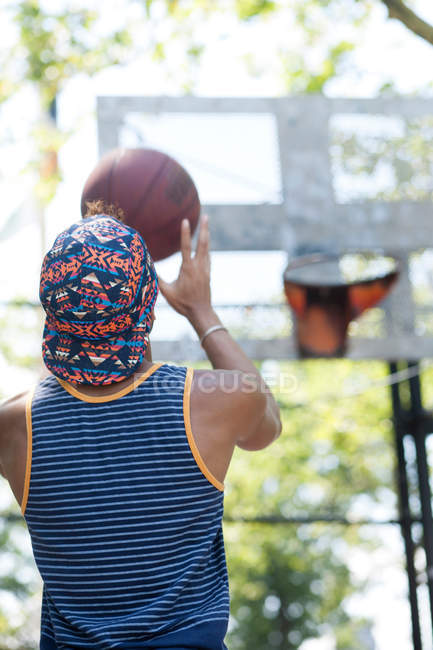 Rear view of young man holding a basketball, ready to shoot — Stock Photo