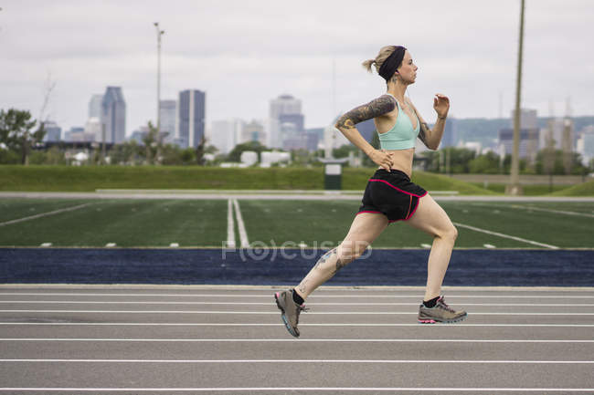 A young blonde woman exercising at running track — Stock Photo