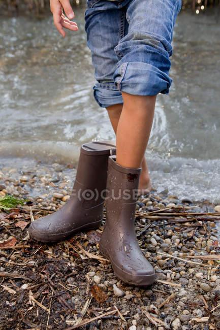 Fille qui décollait les bottes de pluie de l'étang, recadrée tir — Photo de stock