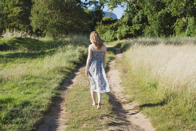 Teenage girl walking on dirt path — Stock Photo