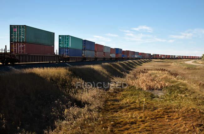 Грузовой поезд над сухим полем на фоне голубого неба — стоковое фото