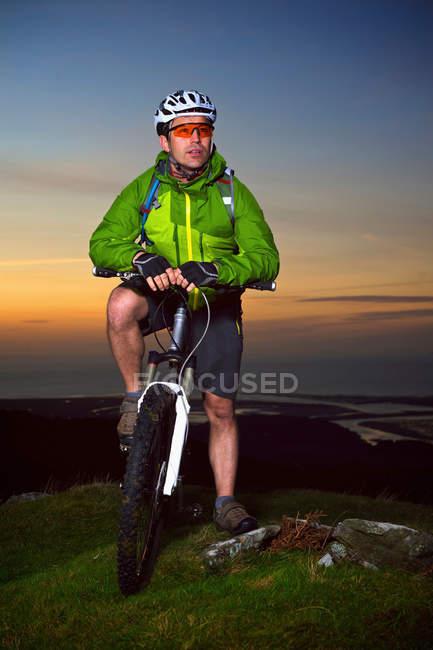 Montanha motociclista de pé no topo da colina — Fotografia de Stock