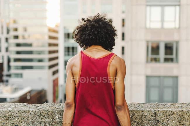 Задній вигляд молодої людини, що дивиться вниз з хмарочос даху — стокове фото
