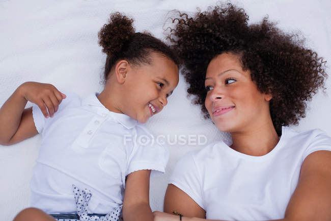 Matriz e filha que colocam na cama — Fotografia de Stock