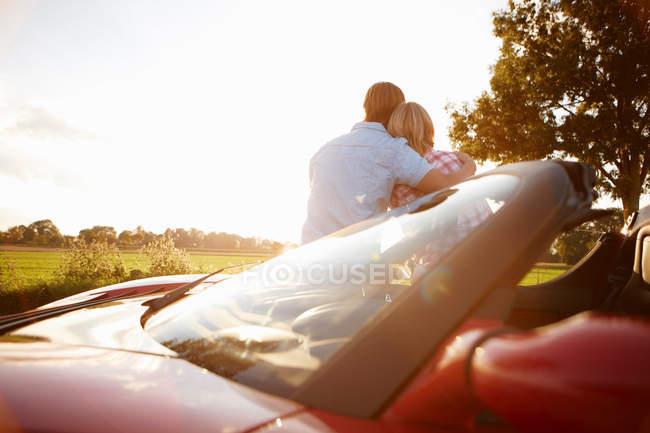 Заднього вигляду пара, сидячи на електричний спортивний автомобіль — стокове фото