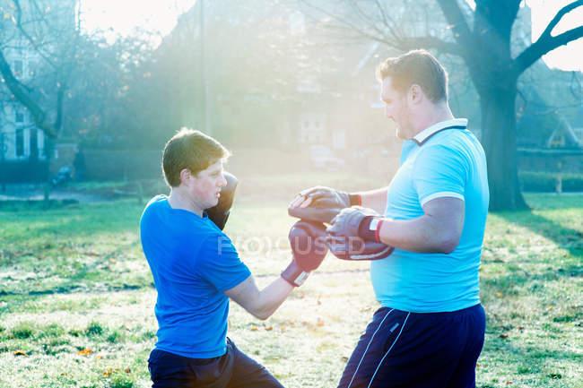 Entrenamiento de boxeador con entrenador al aire libre - foto de stock