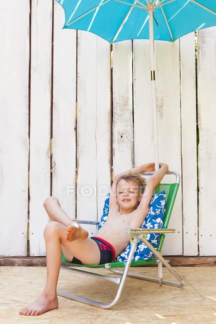 Niño en traje de baño en silla de jardín en interiores - foto de stock