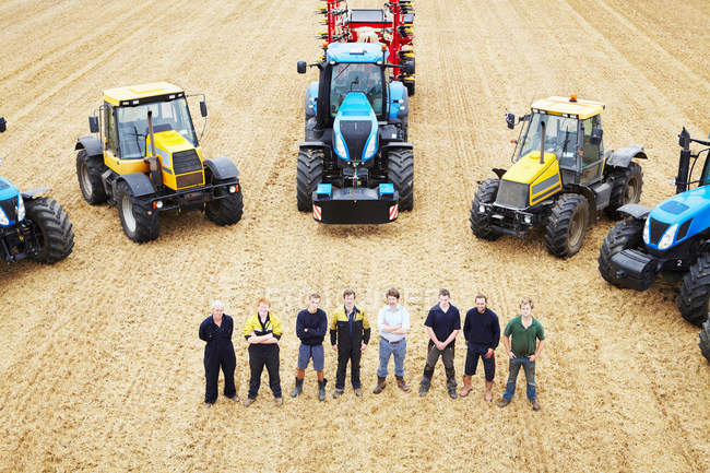 Farmers with tractors in crop field — Stock Photo