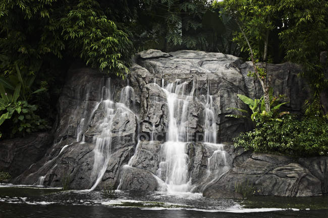 Rocky waterfall in forest lake — Stock Photo
