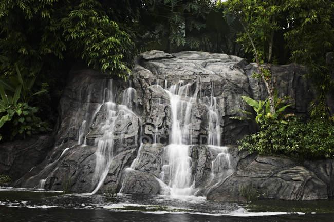 Каменный водопад в лесном озере — стоковое фото