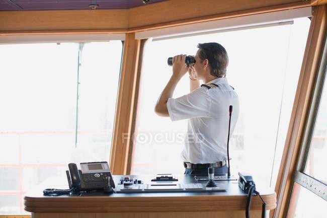 Oficial mirando a través de binoculares - foto de stock