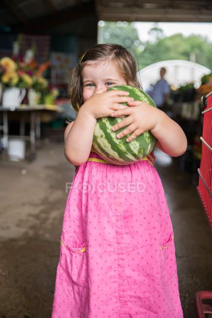 Retrato de niña sosteniendo sandía en el mercado - foto de stock