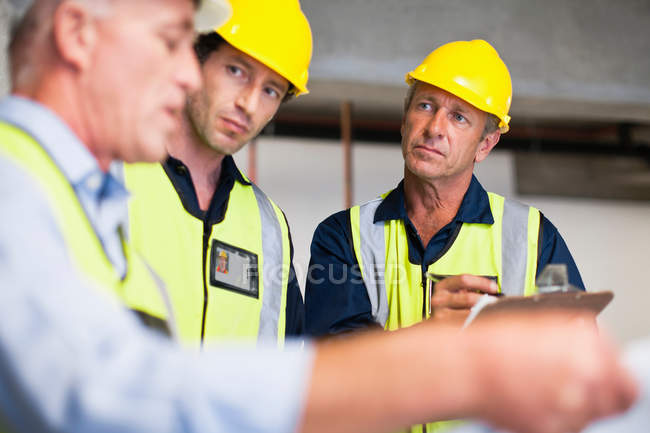 Workers reading blueprints on site — Stock Photo