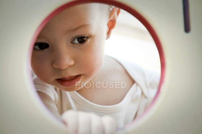 La niña linda en una silla en una habitación - foto de stock