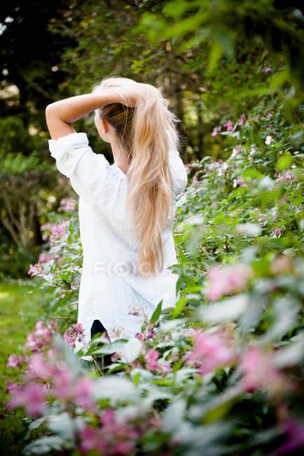 Mulher que está em arbustos da flor — Fotografia de Stock